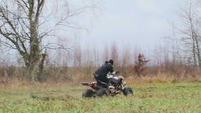 Le type avec le masque sur son visage montant son ATV clips vidéos