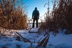 Le type avec le sac à dos se tient au lac et à penser à l'avenir gelés photo libre de droits