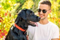 Le type avec un chien marche en parc en automne photo libre de droits