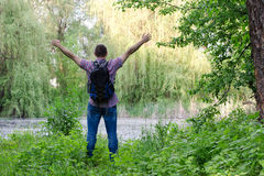 Le type avec un sac à dos se tient sur le rivage d'un lac de forêt avec des bras tendus, une vue arrière Images stock