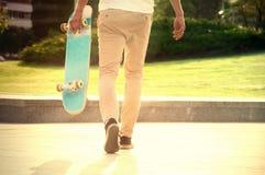 Le type avec une planche à roulettes flâne en parc Photo libre de droits