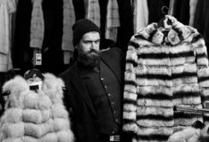 Le type avec le visage adroit montre des manteaux de fourrure dans le magasin de mode photos stock