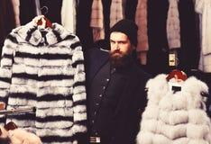 Le type avec le visage adroit montre des manteaux de fourrure dans le magasin de mode photos libres de droits