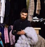 Le type avec le visage choqué regarde dans le portefeuille et tient le manteau Image libre de droits