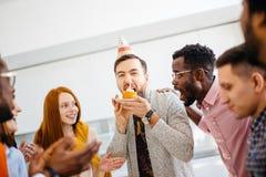 Le type avide essaye de mordre une plus grande paix de gâteau devant des amis Photo stock