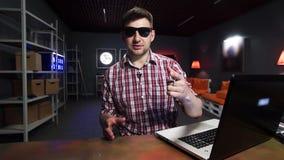 Le type barbu attirant vlogging la séance derrière le bureau avec l'ordinateur portable dans la chambre noire banque de vidéos