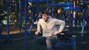 Le type barbu beau établit dehors utilisant la machine d'haltérophilie dans le secteur récréationnel de parc de ville le jour d'é clips vidéos