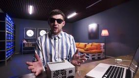 Le type barbu charismatique parle à la boîte de participation de caméra d'alimentation d'énergie avec le refroidisseur banque de vidéos