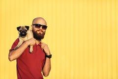 Le type barbu dans des lunettes de soleil tient le chiot de roquet Photographie stock libre de droits