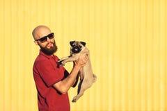 Le type barbu dans des lunettes de soleil tient le chiot de roquet Photos libres de droits