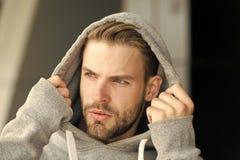 Le type barbu et attirant met dessus le capot Concept de masculinité Homme avec le poil sur le visage sérieux, fond urbain photo stock