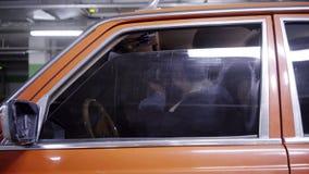Le type barbu mûr avec de longs cheveux foncés et verres optiques s'assied dans la voiture rouge clips vidéos