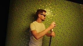 Le type barbu mignon utilisant les lunettes de soleil et le T-shirt blanc chante tenir le microphone banque de vidéos