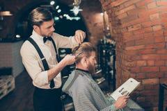 Le type barbu rouge lit un magazine dans un salon de coiffure tandis qu'obtenez photos libres de droits