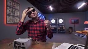 Le type barbu touche ses cheveux ayant la boîte d'alimentation d'énergie avec le refroidisseur mis sur le bureau banque de vidéos