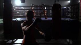 Le type bat une poire, à l'arrière-plan dans l'anneau va des kickboxers de boxe d'entraînement banque de vidéos