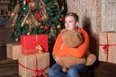 Le type beau étreint l'ours se reposant sous l'arbre entouré par des boîtes de cadeaux Noël et cadeaux image libre de droits