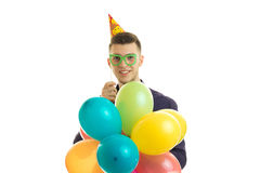 Le type beau avec les verres est les prises joyeuses dans sa main beaucoup de boules et rire colorés Images libres de droits