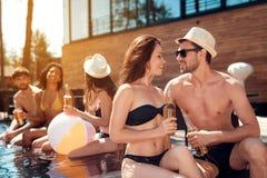 Le type beau dans le chapeau de paille d'été flirte avec la fille dans le maillot de bain se reposant dans la piscine Réception a Image stock