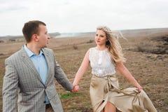 Le type beau et la fille blonde marchant sur le champ, un homme mène une femme tenant la main image libre de droits
