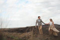 Le type beau et la fille blonde marchant sur le champ, un homme mène une femme tenant la main image stock