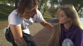Le type beau s'occupe de la fille qui s'est foulée sa jambe banque de vidéos