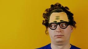 Le type bouclé aliéné avec le strabismus tourne ou roule ses yeux, émotion noire de poils, folle et gaiement humaine, sur le jaun clips vidéos