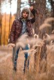 Le type caucasien a reposé son coude sur un arbre dans la forêt d'automne Image libre de droits