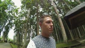Le type caucasien se tient en parc avec le singe sur son épaule qui sautant de lui clips vidéos
