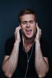 Le type chante à sa chanson préférée écoutant elle sur l'écouteur photo libre de droits