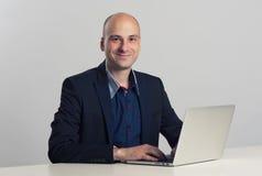 Le type chauve travaille sur son ordinateur portable Image libre de droits