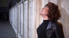 Le type comique habillé comme la femme, les vêtements noirs de port et la perruque, chante l'extérieur clips vidéos