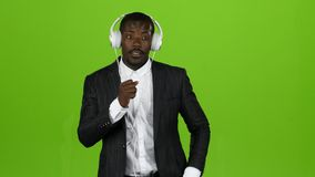 Le type d'africain noir écoute la musique par des écouteurs et chante le long Écran vert banque de vidéos