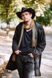 Le type dans le chapeau se tient en parc avec ses mains dans des ses poches photo stock