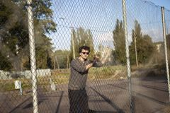 Le type dans des lunettes de soleil s'approchent de la maille de fer Photo stock
