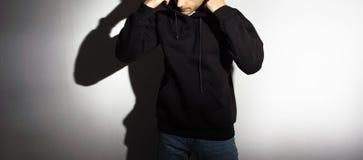 Le type dans le hoodie noir vide, pull molletonné, support, souriant sur un fond blanc, moquerie, l'espace libre, logo, calibre p Photographie stock