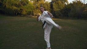 Le type dans le karaté de pratique de kimono, faisant une série de coups par des pieds, s'exerce pendant le matin sur une clairiè clips vidéos