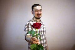 Le type dans la chemise de plaid tient une rose rouge dans sa main Image libre de droits