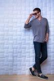 Le type dans la chemise grise de long-douille se tient au mur photos stock