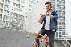 Le type dans la veste de blues-jean continue son vélo d'orange d'épaule Photos libres de droits