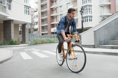 Le type dans la veste de denim va à l'école sur le vélo Cyclistes la route dans la ville Photographie stock