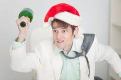 Le type dans le chapeau de Noël se querelle avec la bouteille à disposition images stock