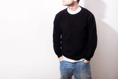 Le type dans le hoodie noir vide, pull molletonné, support, souriant dessus photos libres de droits
