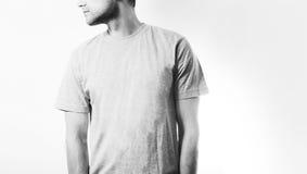 Le type dans le T-shirt gris et blanc vide, support, souriant sur un fond blanc, moquerie, l'espace libre, logo, conception, cali Photos libres de droits