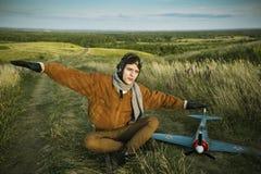 Le type dans le vintage vêtx le pilote avec un modèle d'avion dehors Image stock