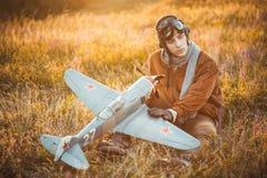 Le type dans le vintage vêtx le pilote avec un modèle d'avion dehors photo libre de droits