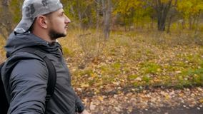 Le type dans les promenades de chapeau par le mouvement lent de forêt d'automne Un endroit agréable Une personne banque de vidéos