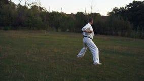 Le type dans le praticien blanc de karaté de kimono exécute Kata Activities Morning sur la clairière dans le parc de ville clips vidéos