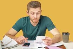 Le type dans le T-shirt vert perplexe étudiant des contrôles et des factures, analyse les coûts de compte sur une calculatrice image libre de droits