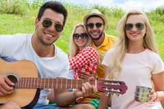 Le type de écoute des jeunes jouant la guitare groupent le jour d'été d'amis Photos stock